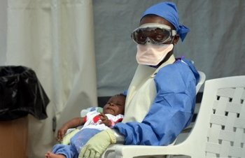 a-liberian-health-worker-holds-a-baby-infected-with-the-ebola-virus-on-october-18-2014-at-an-ebola-treatment-centre-in-monrovia.jpg